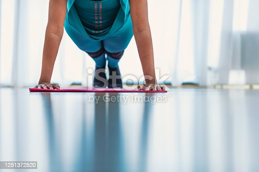 675173150 istock photo Young sporty woman standing in plank pose on fitness mat 1251372520