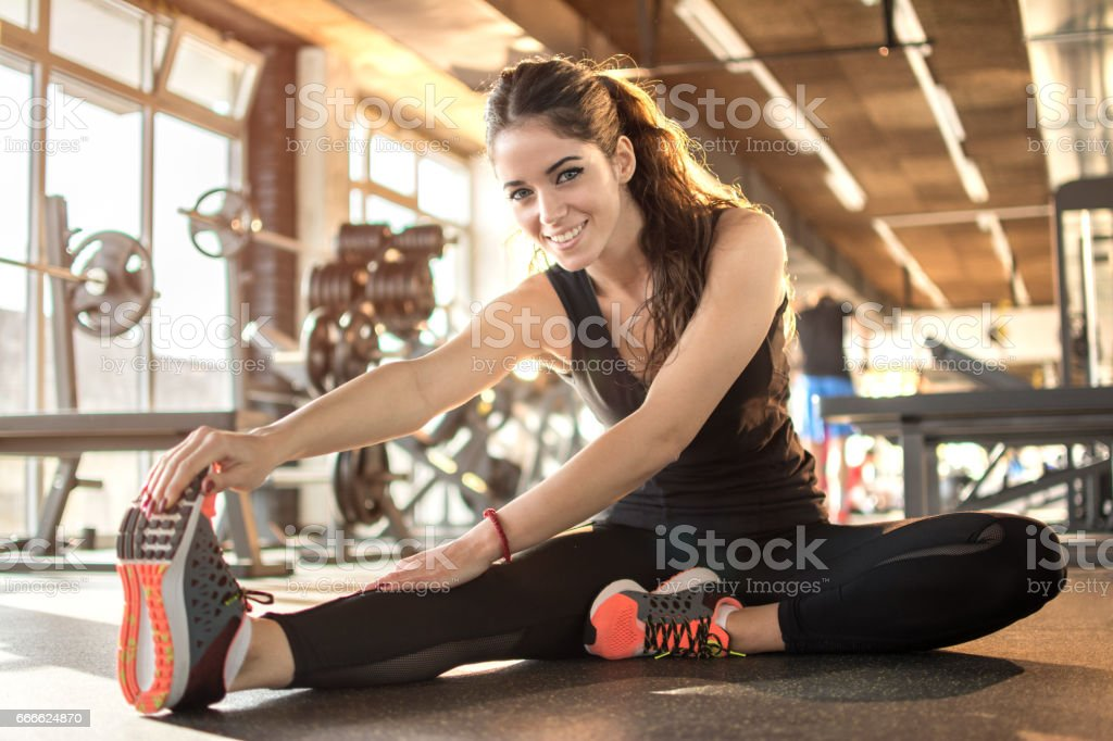Young sporty woman stretching at gym. - foto de stock