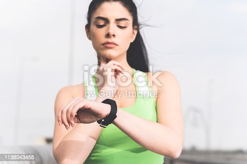 Closeup image of sporty girl measuring her pulse and looking at her smartwach, Active lifestyle and recreation concept