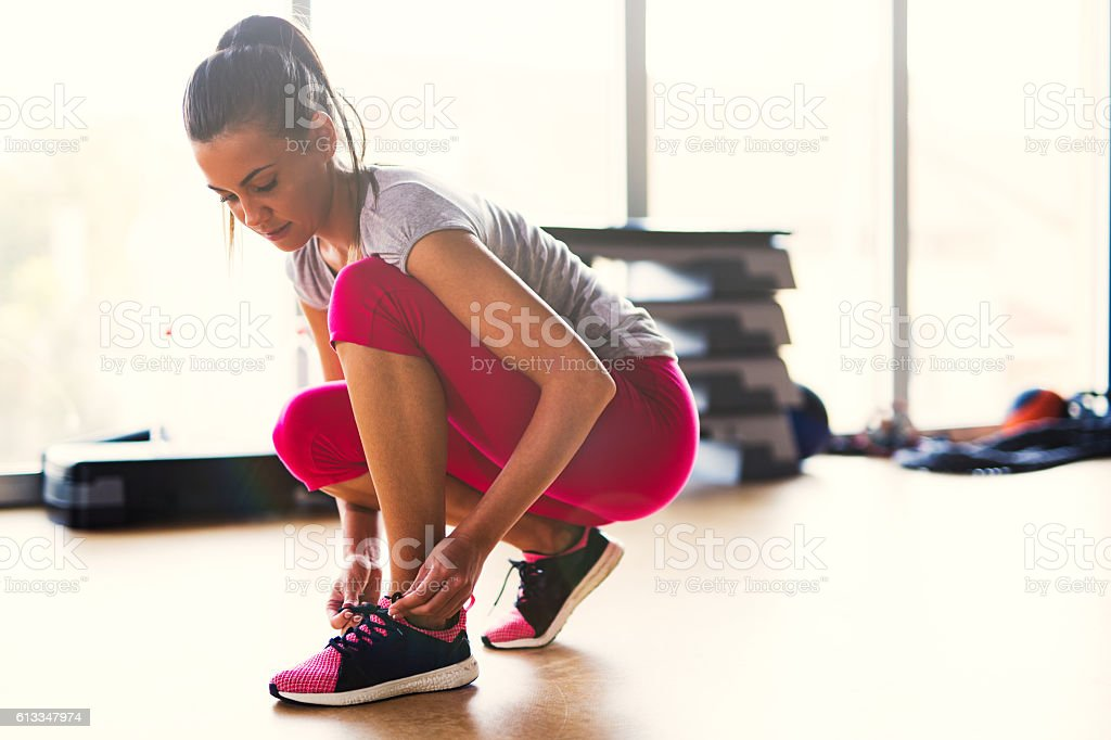Young sporty woman tying shoelaces  at the gym. stock photo