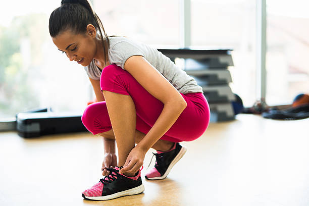 young sporty woman tying shoelaces  at the gym. - tupfen schuhe stock-fotos und bilder