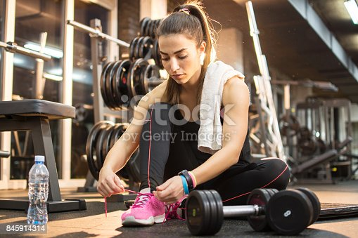 Young sporty woman tying shoes while sitting on floor in gym.