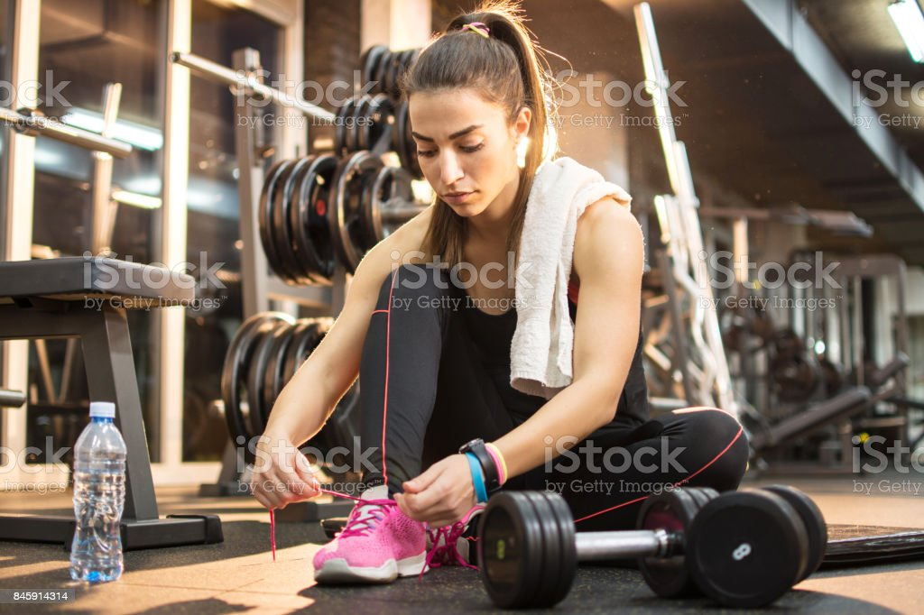 Young sporty woman tying shoes while sitting on floor in gym. stock photo