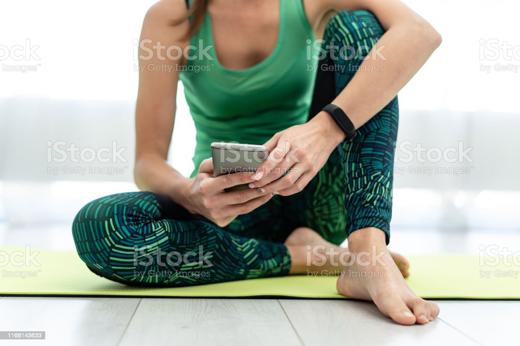 Young sporty woman using smartphone, sitting on fitness mat - Royalty-free Adult Stock Photo
