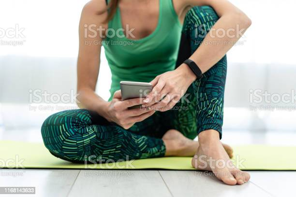 Young Sporty Woman Using Smartphone Sitting On Fitness Mat Stock Photo - Download Image Now