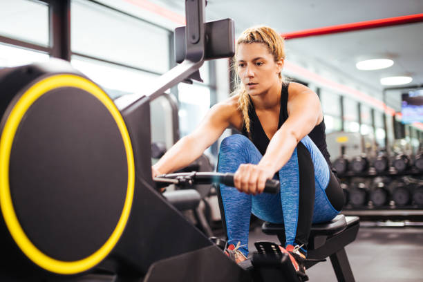 Young sporty woman working out on a rowing machine in a gym stock photo