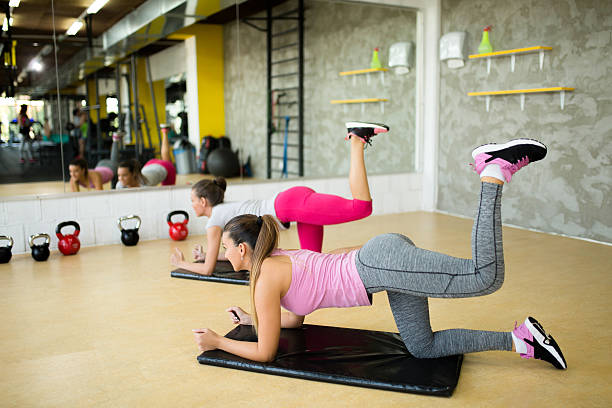 Young sporty women doing leg and buttocks exercises - foto de stock