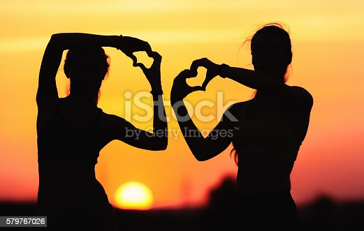 istock Young sporty women holding hands in heart shape at sunset 579767026
