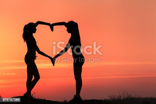 istock Young sporty women holding hands in heart shape at sunset 579767086