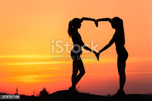 istock Young sporty women holding hands in heart shape at sunset 579767158
