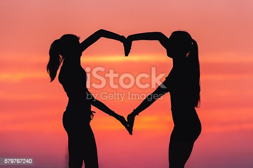 istock Young sporty women holding hands in heart shape at sunset 579767240