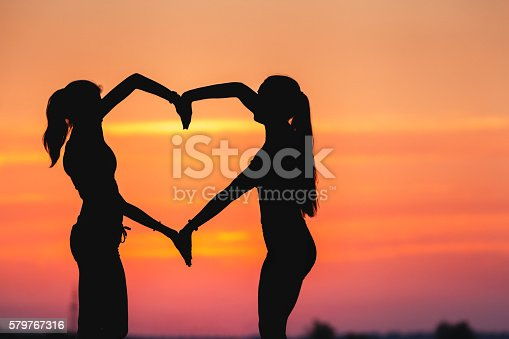 istock Young sporty women holding hands in heart shape at sunset 579767316