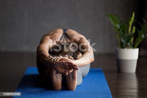 istock Young sporty yogi woman doing paschimottanasana pose 1036550580