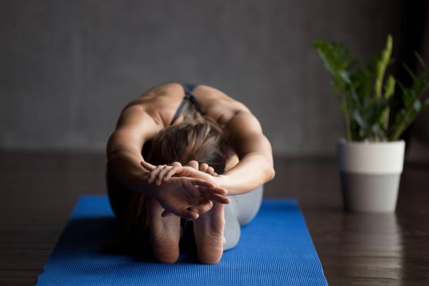 junge sportliche yogi frau paschimottanasana pose zu tun - yin yoga stock-fotos und bilder