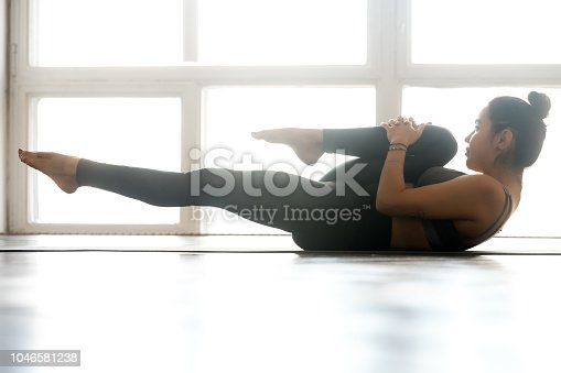 914755474 istock photo Young sporty yogi woman practicing, doing exercise 1046581238