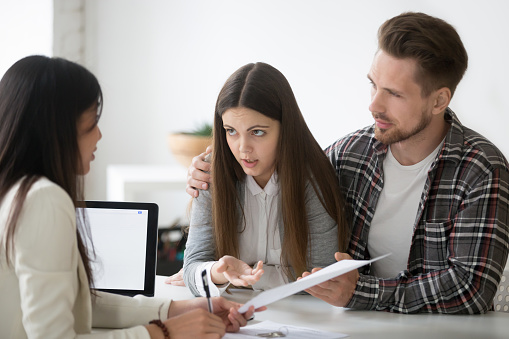 istock Young spouses having dispute about house buying with realtor 990458634