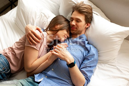 Top view of man and woman in love sleeping in comfortable bed together at home