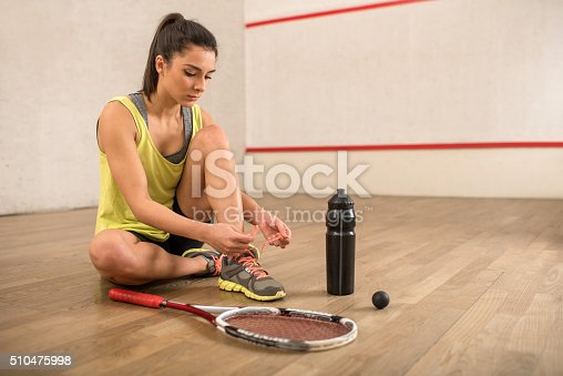 Young woman tying shoelaces and preparing for racketball.