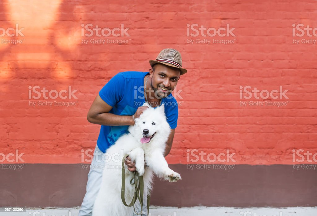 Young Sri Lankan and his fluffy white dog against the background of a red brick wall. stock photo