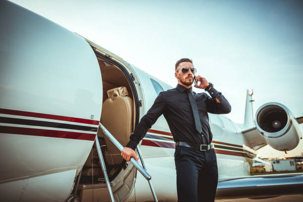 young stern rich man disembarking from a private jet while talking on a mobile phone - consumo exibicionista imagens e fotografias de stock
