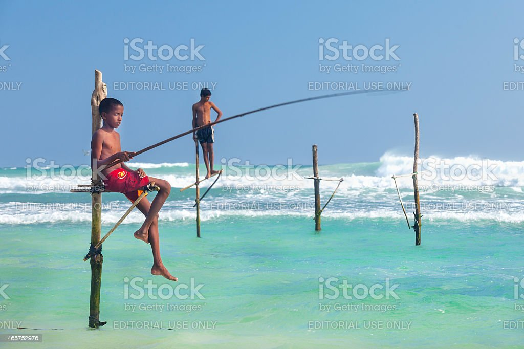 Young stilt fishermen at Hikkaduwa Beach. stock photo