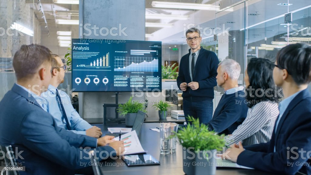 Young Stock Trader Shows to the Executive Managers Cryptocurrency and Trade Market Correlation Pointing at the Wall TV. stock photo