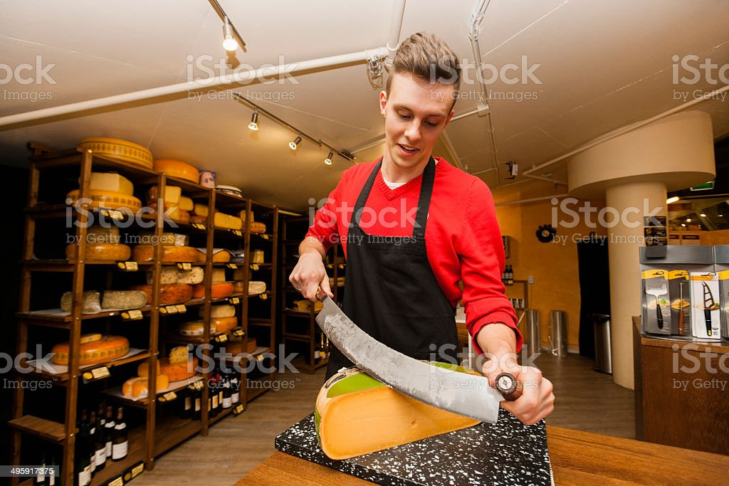 Young store clerk cutting cheese at counter - Royalty-free 18-19 Years Stock Photo