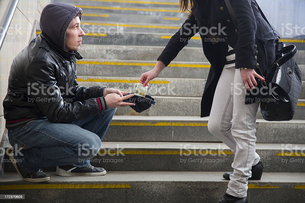Young street begger...begging on stairway...woman is giving him some cash stock photo