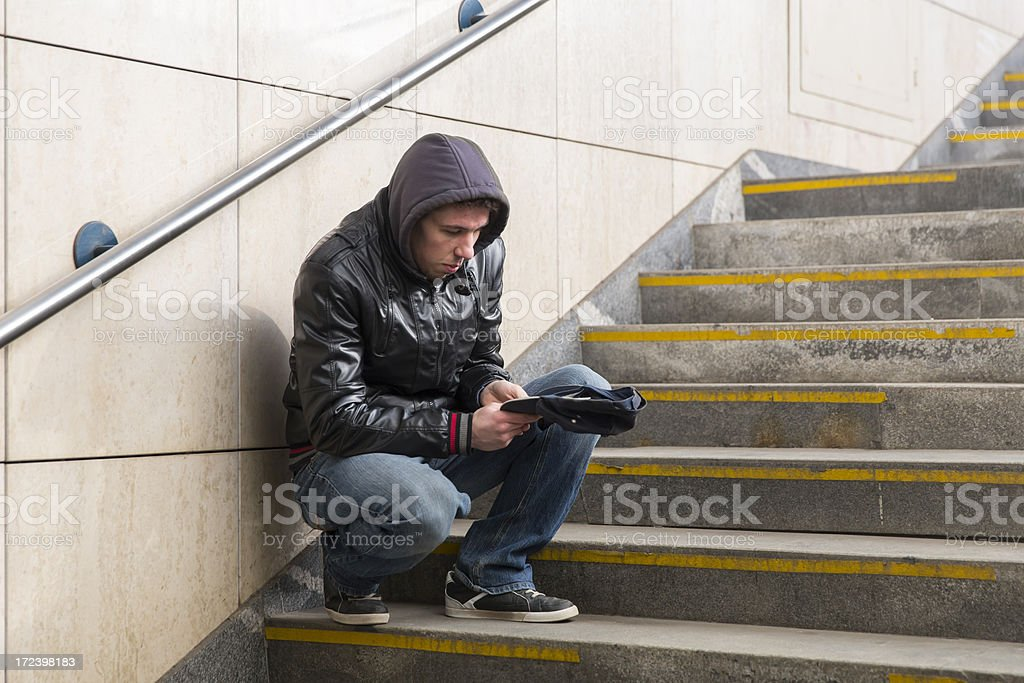 Young street begger...probably an addict, begging on a stairway stock photo