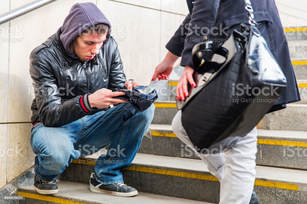 Young street begger...probably an addict begging on a stairway...woman is giving him some cash stock photo
