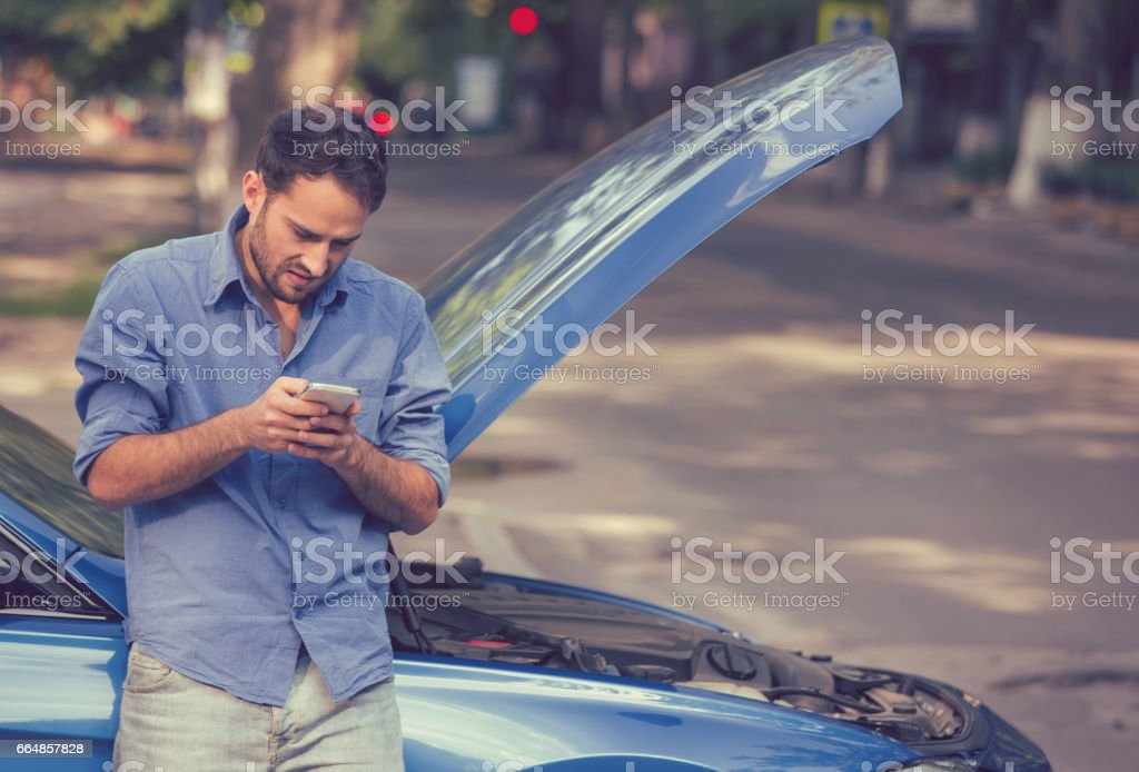 young stressed man driver having trouble with his broken car looking in frustration at failed engine stock photo