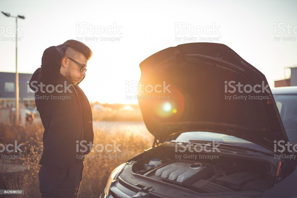 Young stressed man having trouble with his broken car looking in frustration on failed engine stock photo