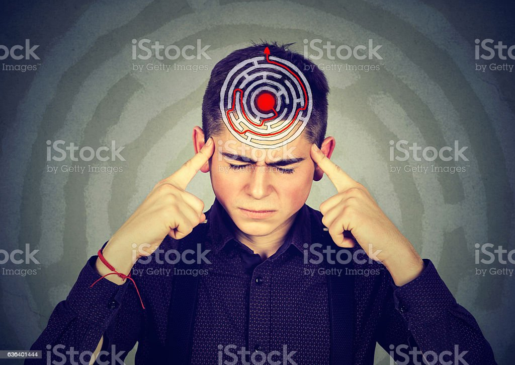 Young stressed man solving puzzle stock photo