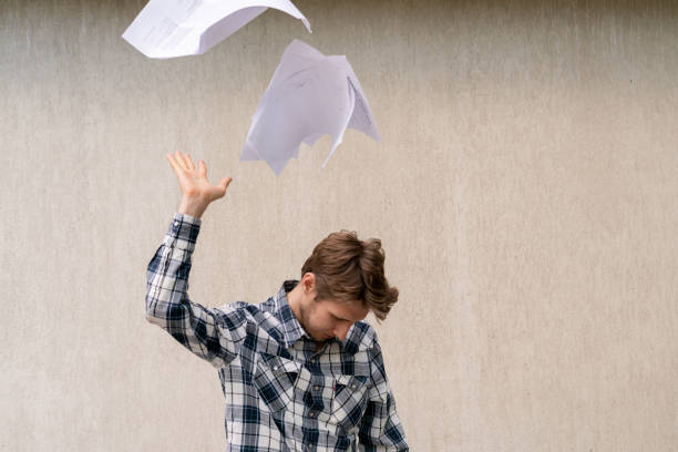young stressed man throw crumpled paper files in the air, freedom concept stock photo