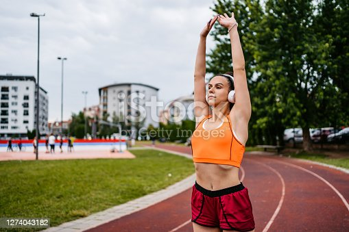 Young Caucasian athlete woman is doing warm up and stretching before active training on running track.
