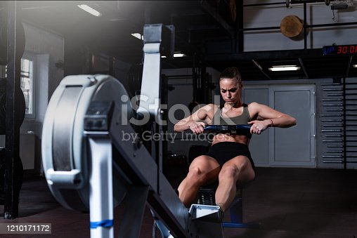 Young strong fit sweaty powerful attractive muscular woman with big muscles doing hard core row heavy cross training workout on indoor rower at the gym real people exercise