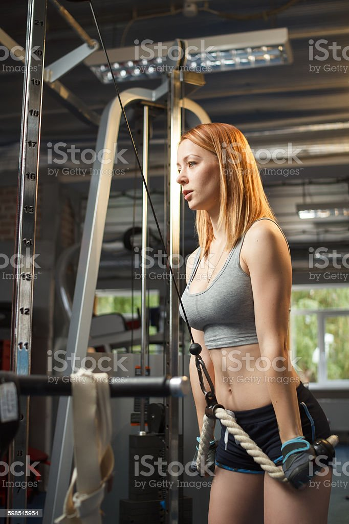 Young strong girl do exercises on cable crossover machine photo libre de droits