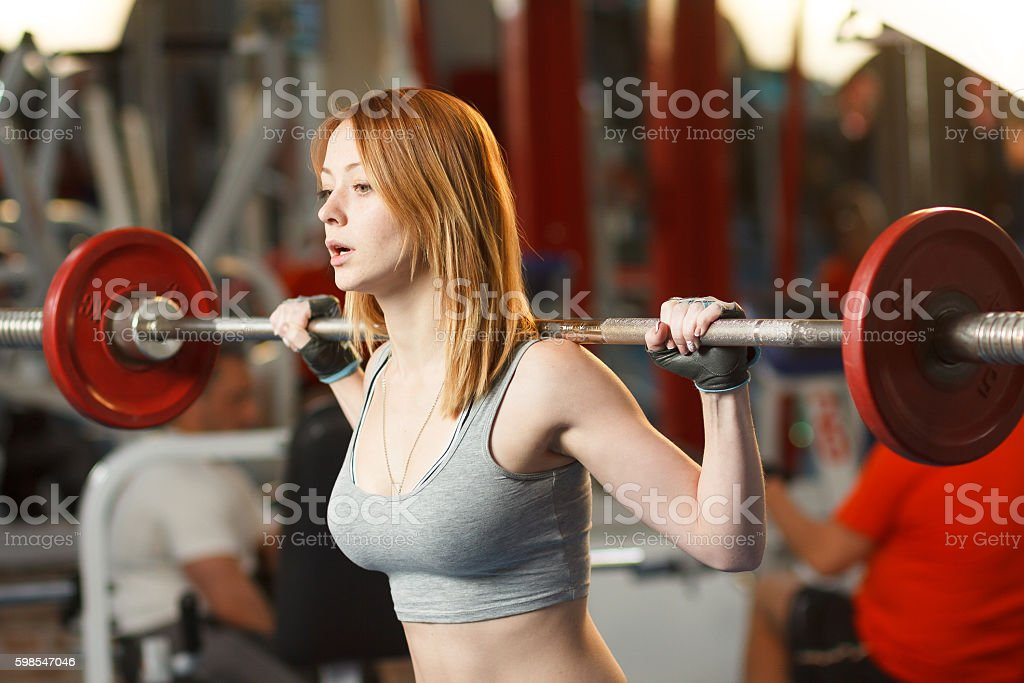 Young strong girl do squats with a barbell photo libre de droits