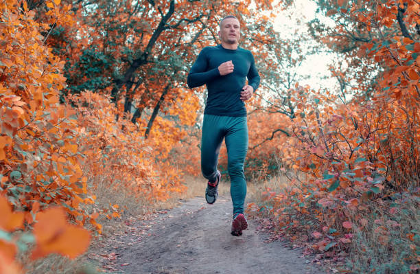 young strong man in a black sports leggins, shirt and sneakers runs on the  red autumn forest - carpet runner stock photos and pictures