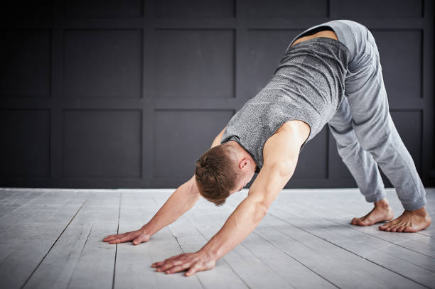 Young strong man practices yoga at the yoga studio stock photo