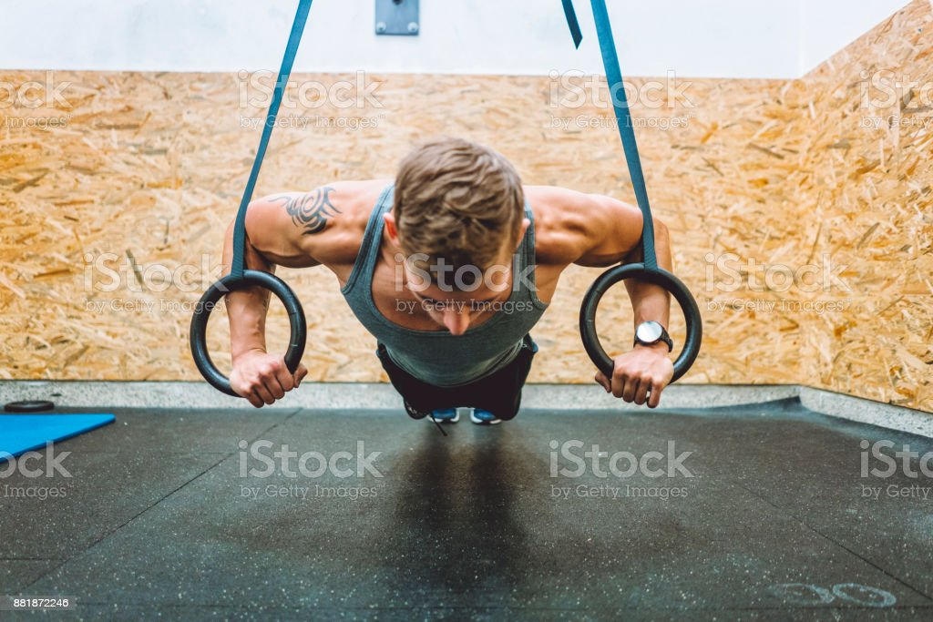 Young strong man practising pull ups with gymnastic rings stock photo