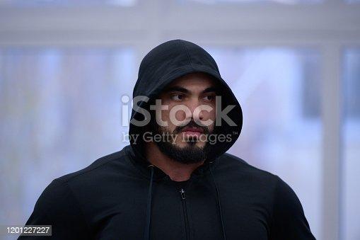 strong man with beard wearing black sportswear hoodie in sport gym