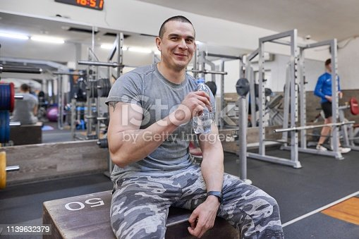 istock Young strong muscular man in gym drinking water from bottle 1139632379