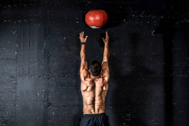 young strong sweaty focused fit muscular man with big muscles doing throwing medicine ball up on the wall for training hard core workout in the gym real people selective focus - testosterone stock pictures, royalty-free photos & images