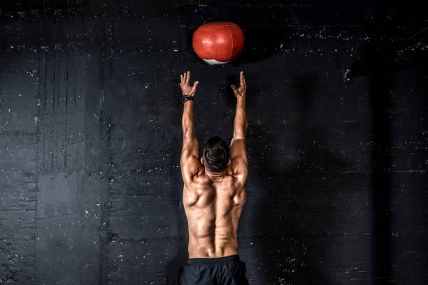 joven fuerte sudoroso enfocado ajuste hombre musculoso con grandes músculos haciendo lanzar la pelota de medicina en la pared para entrenar entrenamiento de núcleo duro en el gimnasio personas reales enfoque selectivo - macho fotografías e imágenes de stock