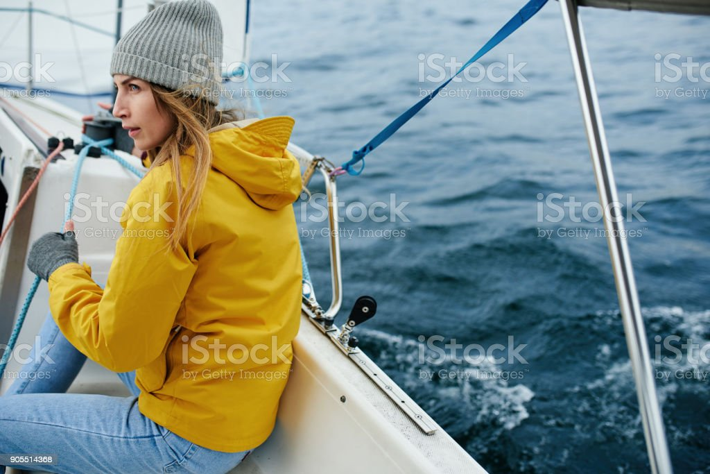 Young strong woman sailing the boat stock photo