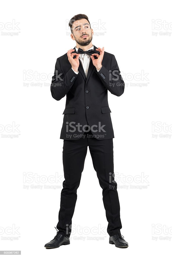 Young stubble groom adjusting bow tie looking up. stock photo