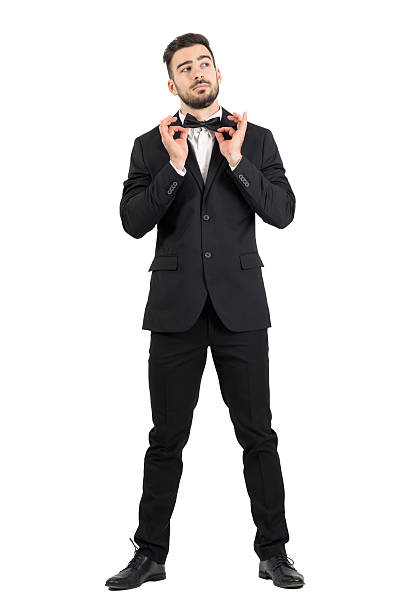 Young stubble groom adjusting bow tie looking up. Young stubble groom adjusting bow tie looking up. Full body length portrait isolated over white studio background. tuxedo stock pictures, royalty-free photos & images