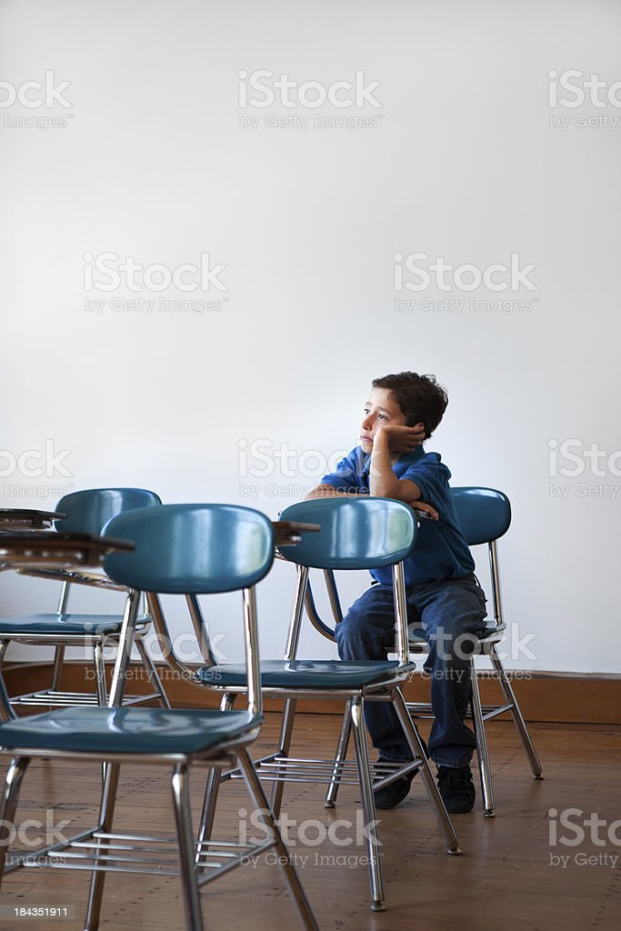 young student alone in a classroom stock photo