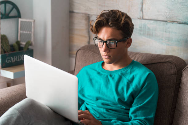 Young student at home in smart working with college classes and lessons use laptop computer - young people with eyeglasses and technology - modern lifestyle with online courses and school stock photo